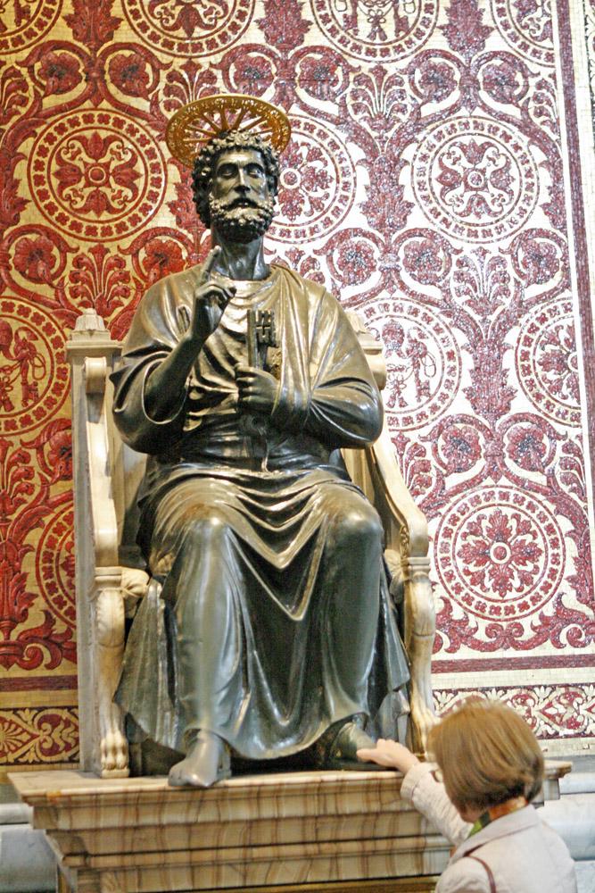 Die Petrusstatue im Hauptschiff des Petersdoms, mit dem segenbringenden abgeflachten rechten Fuß, wird von zahlreichen Gläubigen verehrt.