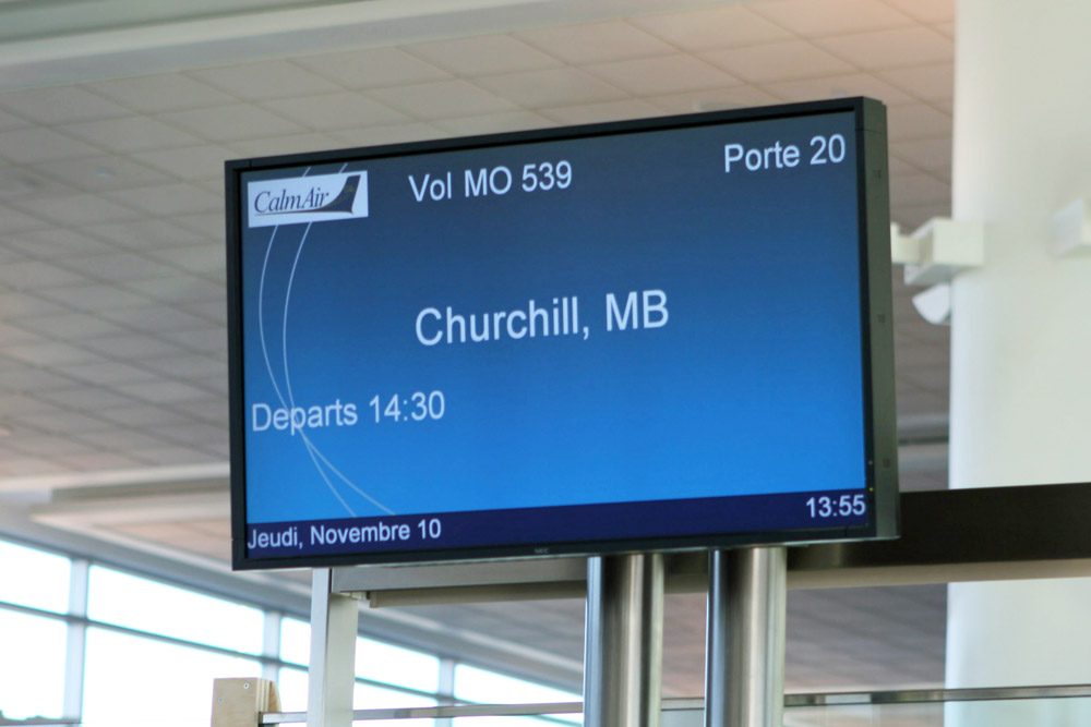 Eine Abflugtafel auf dem Flughafen von Winnipeg zeigt den Abflug eines Calm Air Fluges nach Churchill an.