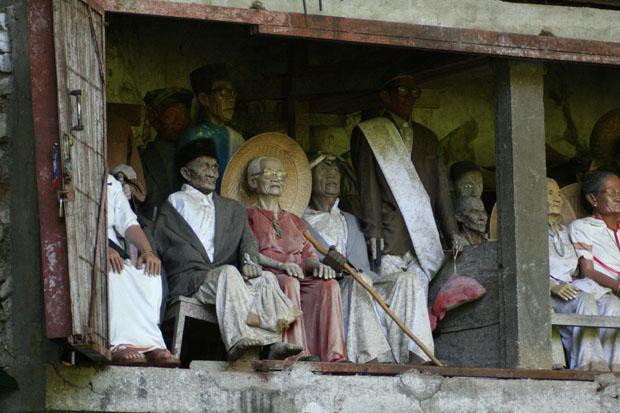 Vor den Gräbern erinnern handgeschnitzte Puppen an das Aussehen der Verstorbenen.