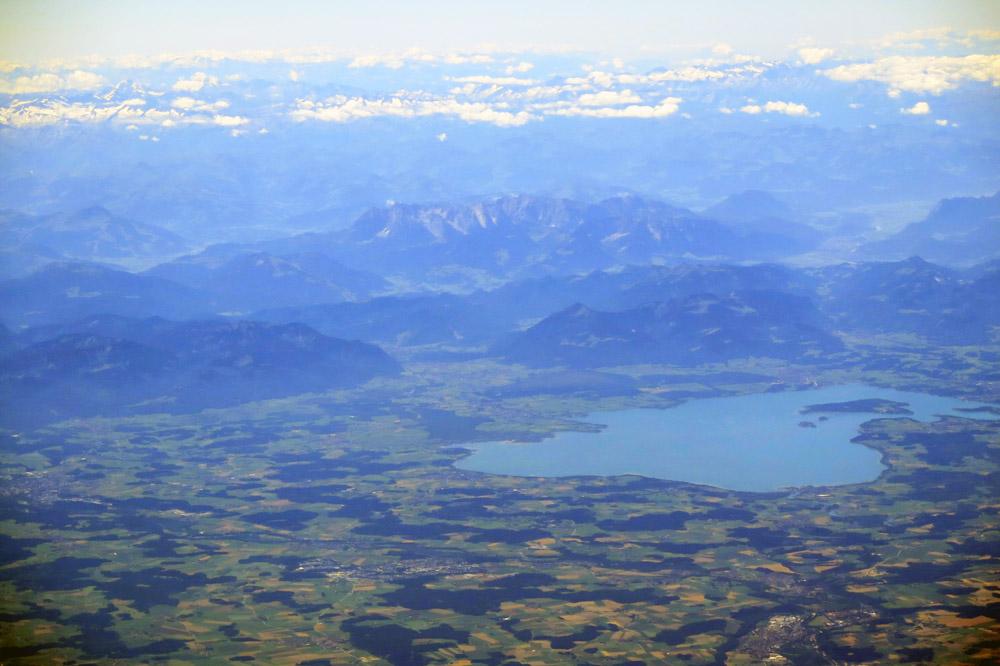 Blick über den Chiemsee von oben mit den Bergen im Hintergrund