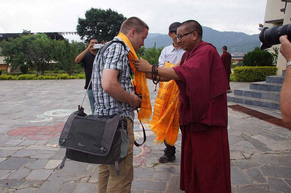 Ein Lama überreicht in einem Kloster einem Besucher einen Schal