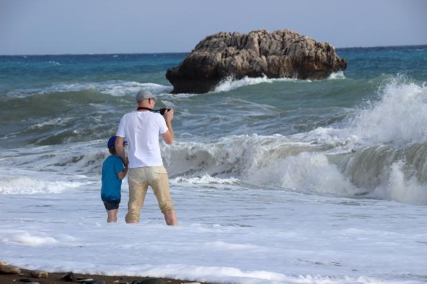 Ein junger Vater erfreut sich mit seinem Sohn an den Wellen