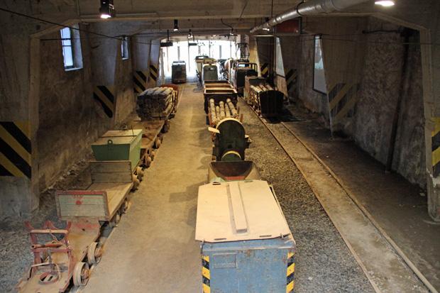 In einem kleinen Bahnhof stehen alte Grubenbahnen