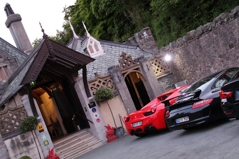 Ein Ferrari und ein Porsche parken vor dem Chateau Rhianfa