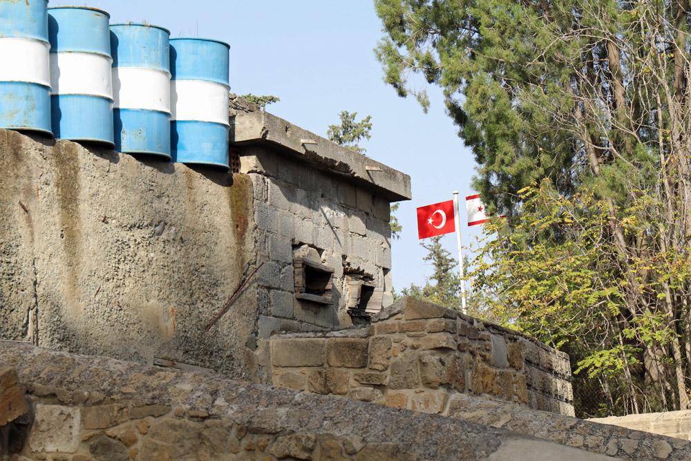 Ein typisches Bild in der Pufferzone Nikosias. Links die blau weißen Absperrungen, rechts die türkische Flagge