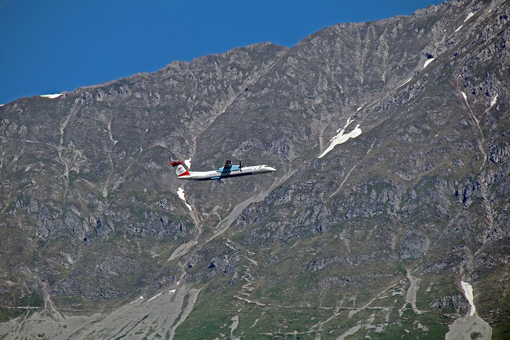 Der Blick fällt auf die schroffen Felswände der Nordkette in Innsbruck. Hier fliegt ein Flugzeug vorbei.