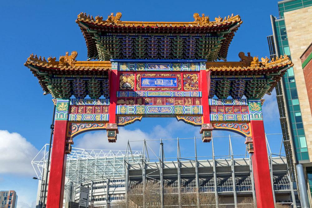 Tor am Eingang zu Chinatown im Newcastle mit dem Fußballstadion St. James Parc
