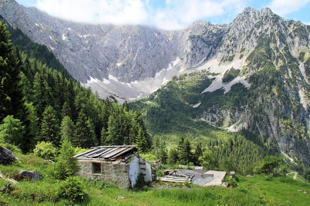 Ruinen der verfallenen Jöchlalm am Heuberg in Österreich mit Blick auf die Nordwände des Zahmen Kaisers in Tirol