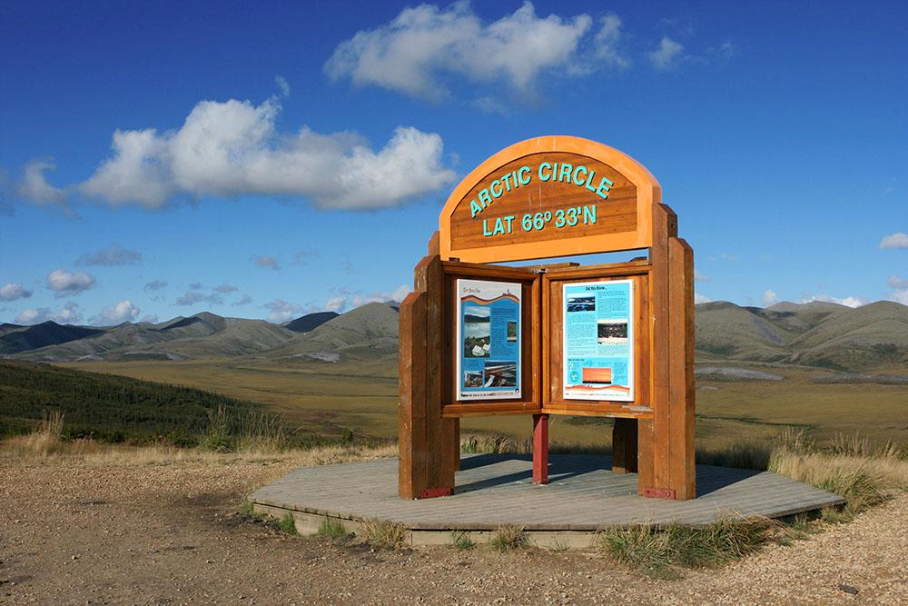 Der Dempster Highway überquert den Polarkreis in Kanada. Ein Schild weißt darauf hin