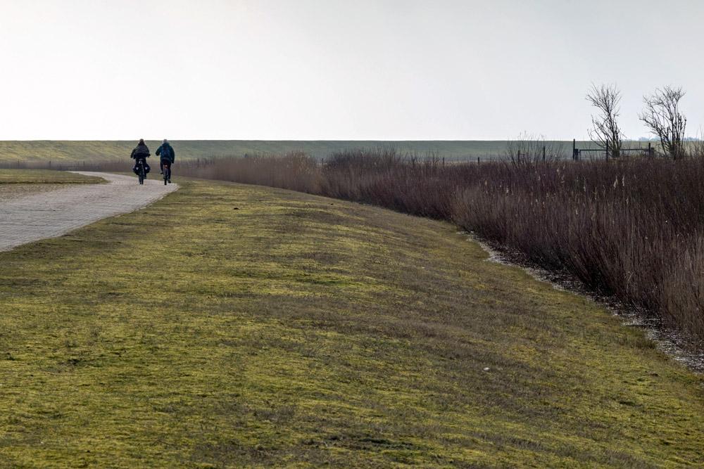 Am Deich entlang führt ein Fahrradweg.